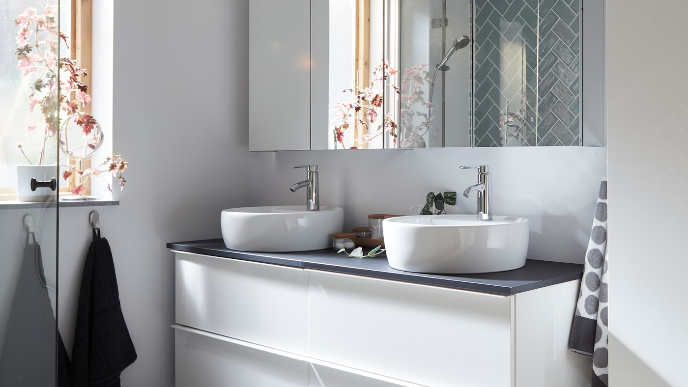 A bathroom with a white high-gloss wash-stand with two drawers and a grey countertop with two white wash-basins and a mirror.