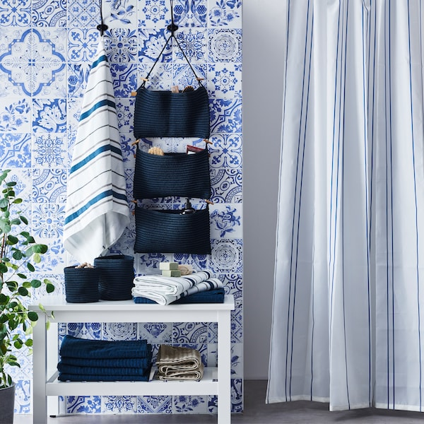 A bathroom with blue and white patterned wall tiles, striped shower curtain, hanging storage and towels folded on a storage unit.