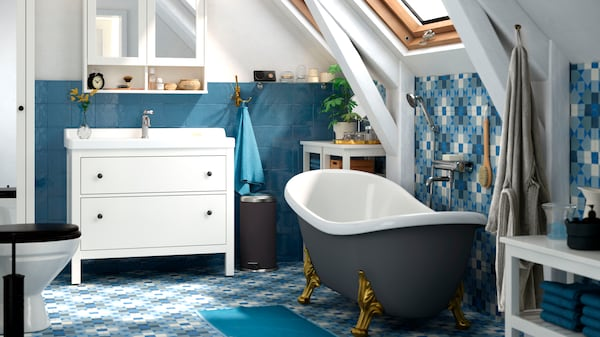 A bathroom with blue floor and wall tiles, a free-standing bath tub, and white wash-basin with mirrored cupboards above.