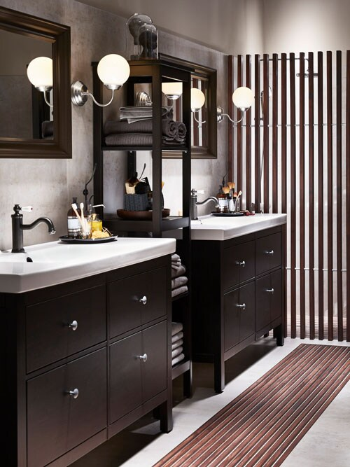 A bathroom with dark wood furniture and white sinks.