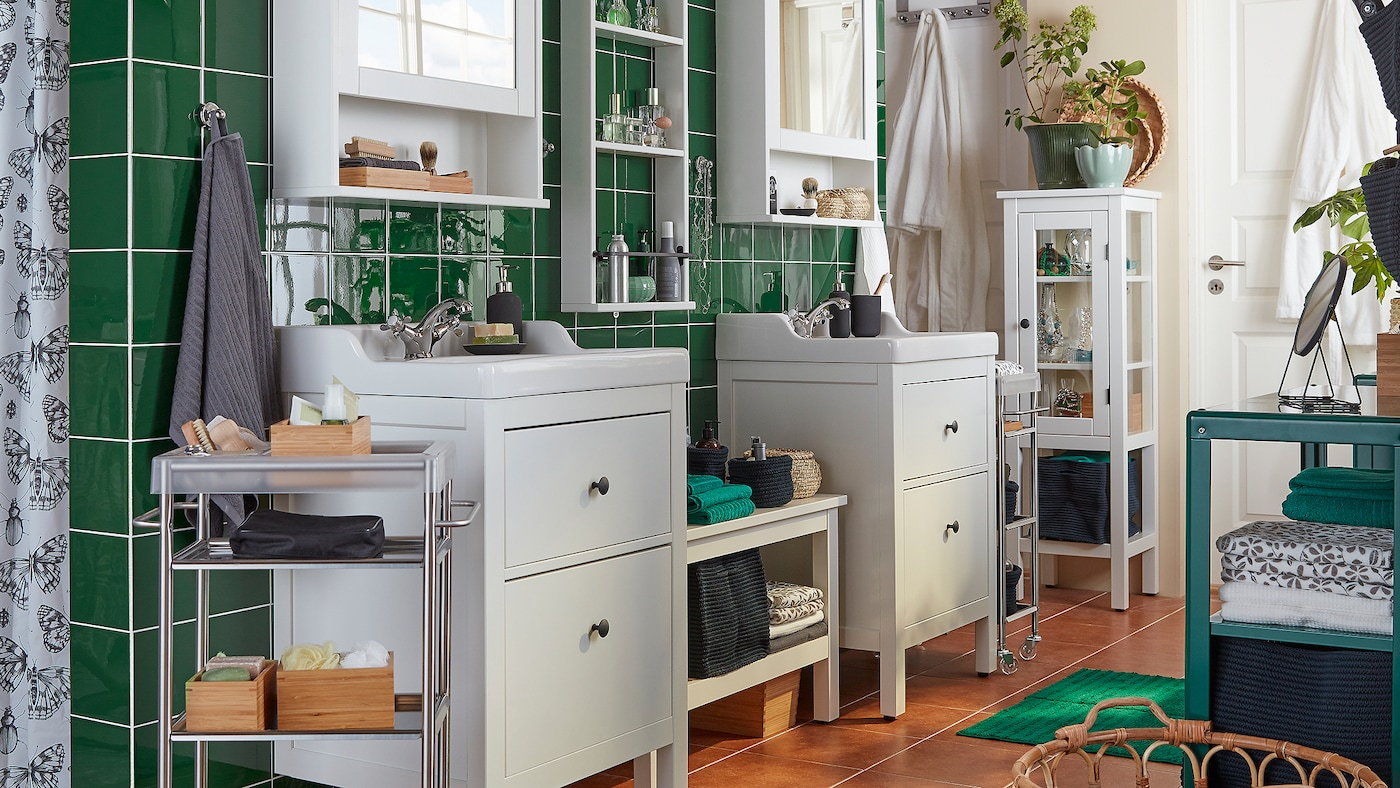 A bathroom with green tiles, two white HEMNES sink vanities and mirror cabinets, towels and accessories on display.