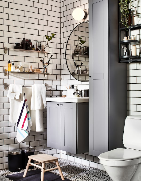 A bathroom with grey ENHET bathroom furniture and wall mounted BROGRUND glass shelves, one for him and one for her.