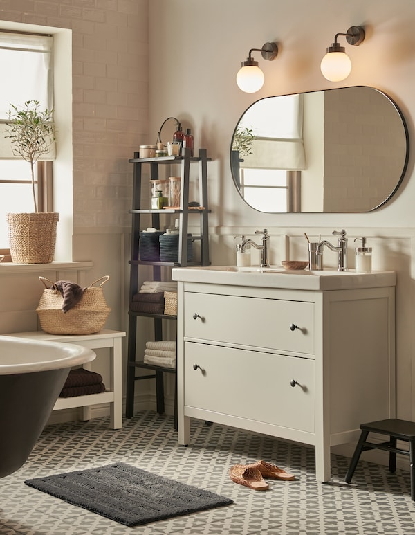 A bathroom with Moroccan style tiles and neutral colours, a HEMNES wash-stand with two drawers, and a large mirror.