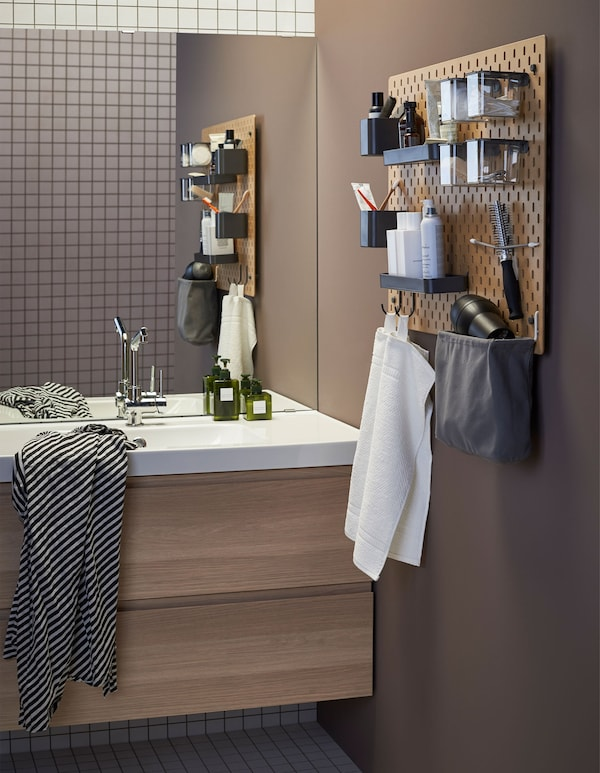 A bathroom with wall sink unit and pegboard holding bathroom accessories.