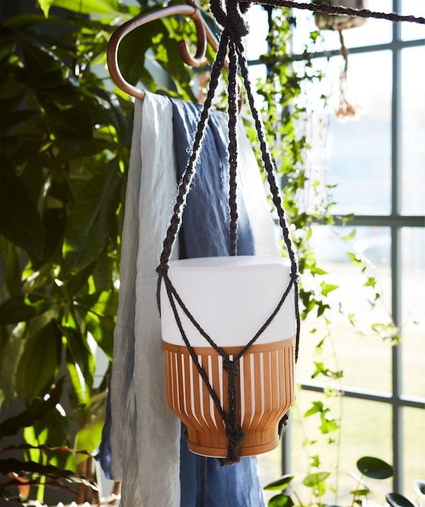A battery charged MULLBACKA LED table lamp hanging freely, surrounded by plant greenery.