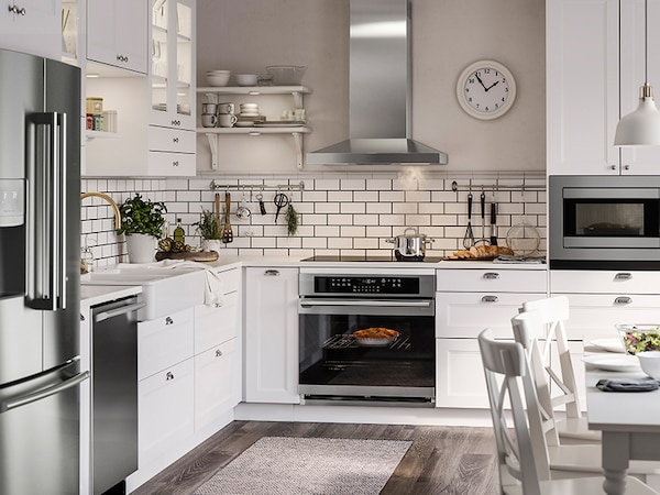 A beautiful modern kitchen with white cabinets and black stainless steel appliances.