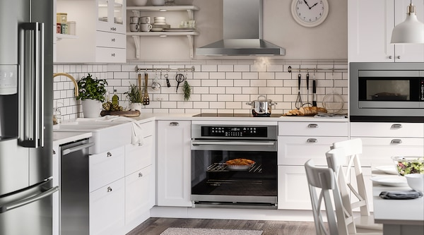 A beautiful modern kitchen with white cabinets and stainless steel appliances