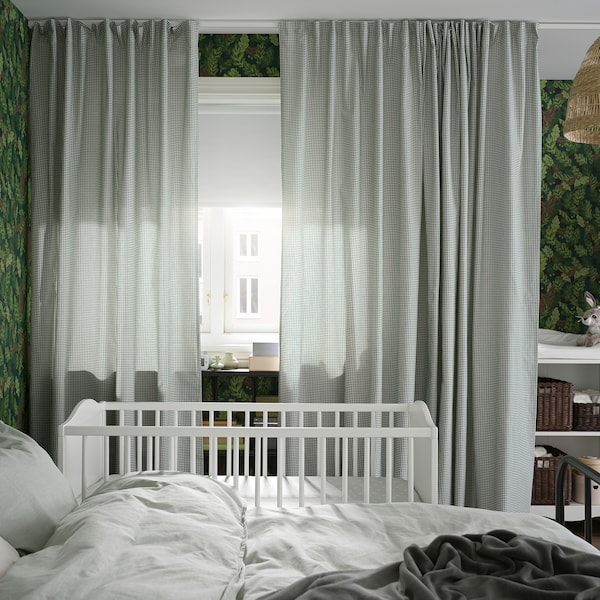 A bed and cot stand by a window with green/white curtains and a white block-out roller blind that covers half the window.