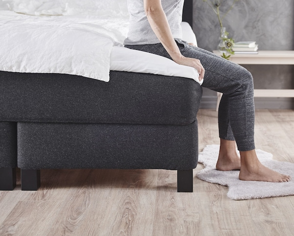 A bed base with mattress on top that a person is sitting on.