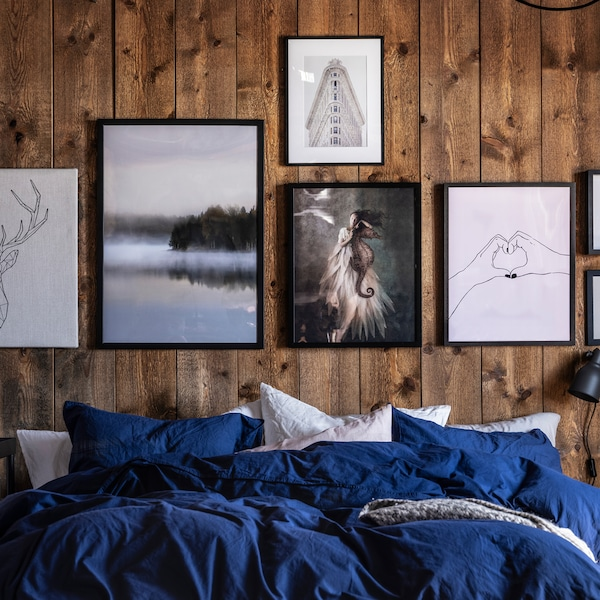 A bed covered in a mix of white and blue bed linen in front of a wooden wall covered with different pictures in black frames.