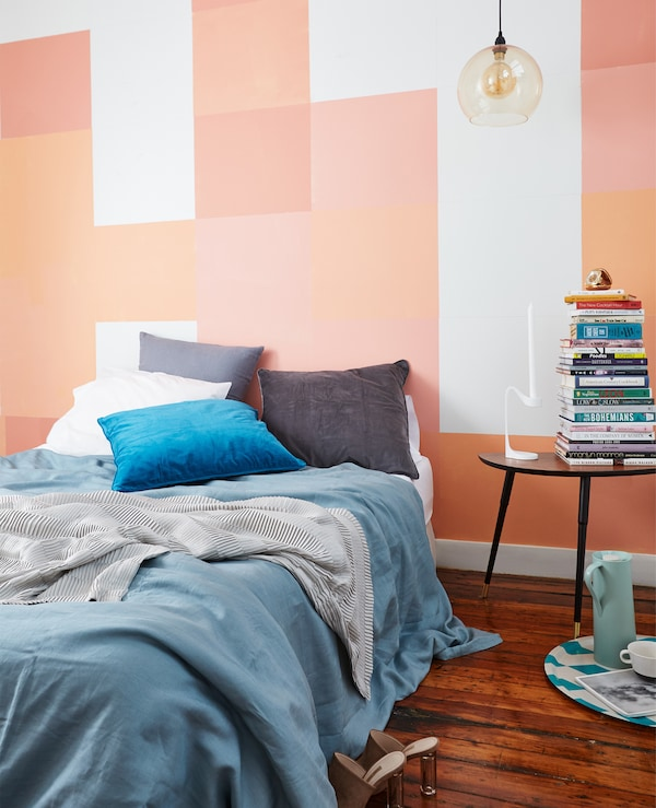 A bed dressed with blue and grey textiles against a wall painted with pink, coral and orange squares.