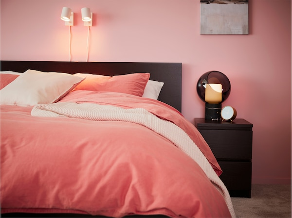 A bed frame and bedside table in black-brown, bed textiles in light brown-red and white wall lamps.