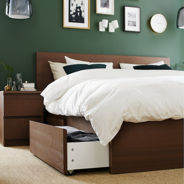 A bed frame and bedside table in brown stained ash veneer and quilt cover and pillowcases in white.