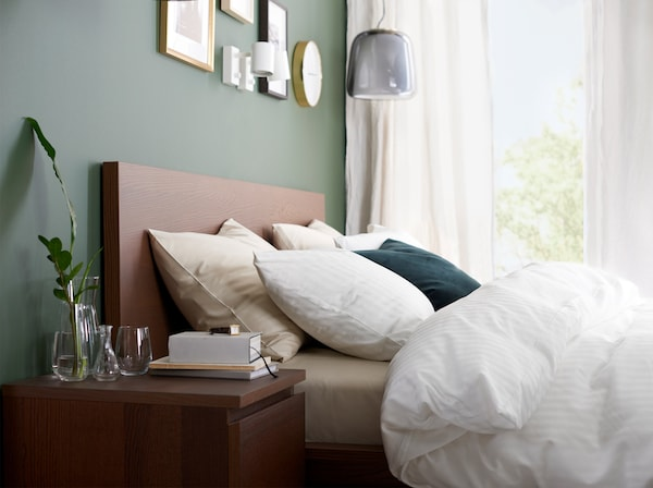 A bed frame and bedside table in brown stained ash veneer and a quilt cover, pillowcases and curtains in white.
