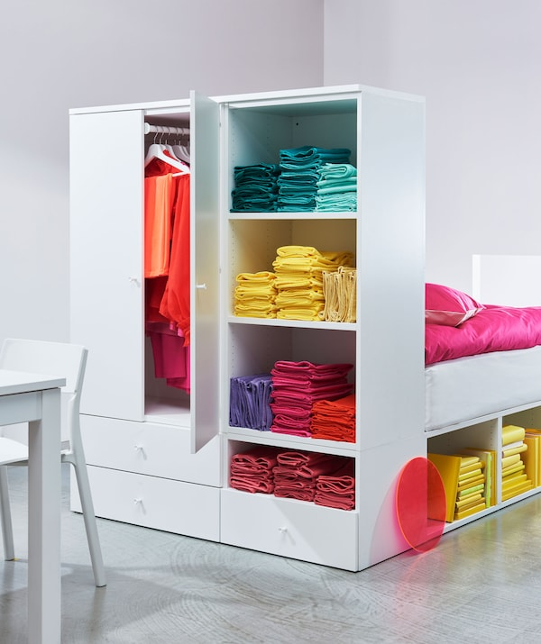 A bed frame which has a built-in wardrobe as its headboard with colourful clothes stored inside.