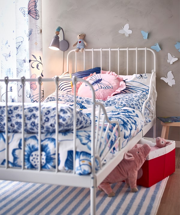 A bed frame with blue and white floral bedding, cushions and curtains with a butterfly motif, and toys under the bed.