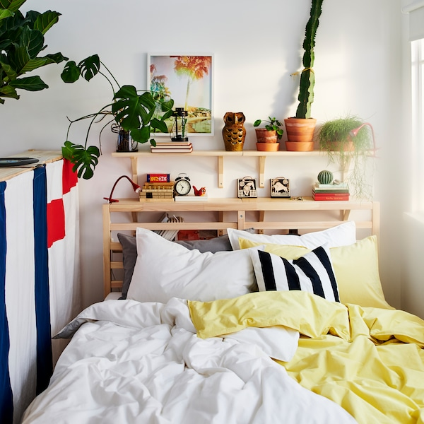 A bed in a small room with yellow and white bed linen and a pine shelving unit behind it holding plants and small objects.