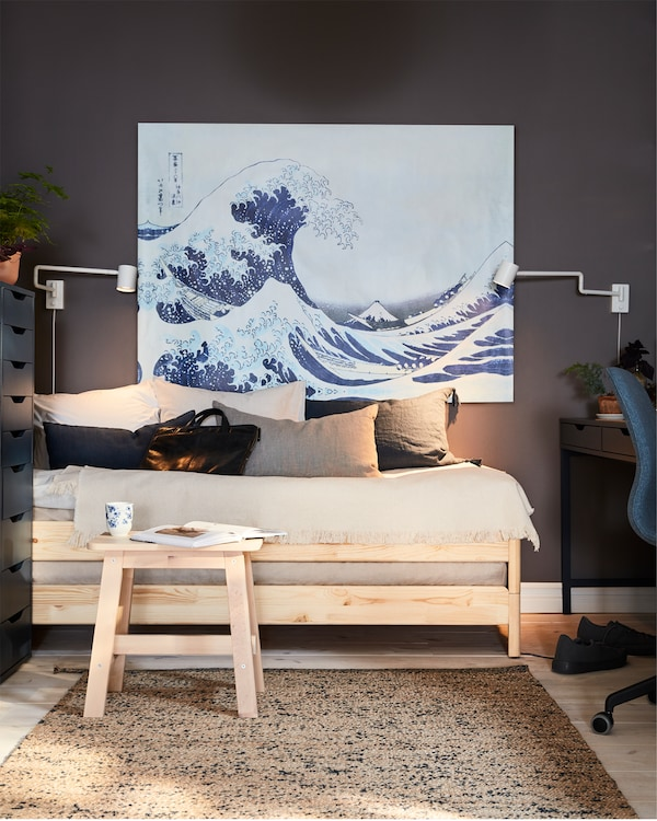 A bed in pine and a birch stool with a book and a mug in front, a big painting with a wave and two white wall-mounted lamps.