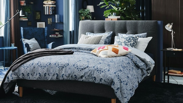 A bed in the middle of a room with a gray headboard and blue and white patterned bedding.