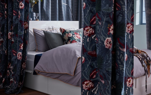 A bed is framed with several curtains of the dark blue, floral patterned IKEA FILODENDRON fabric.