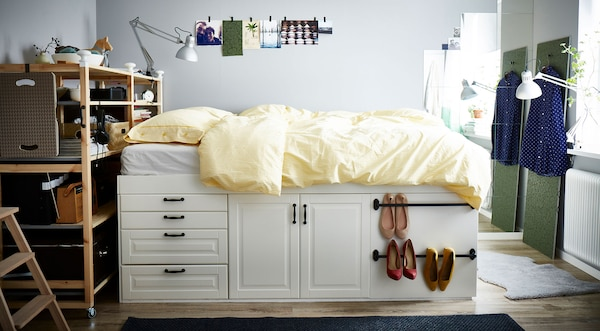 A bed made from METOD kitchen cabinets with a yellow quilt in a small room.