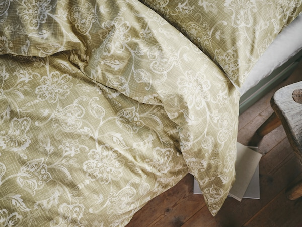 A bed made with IKEA JUNIMAGNOLIA bed linen in cotton with a classic, white and green flower print.