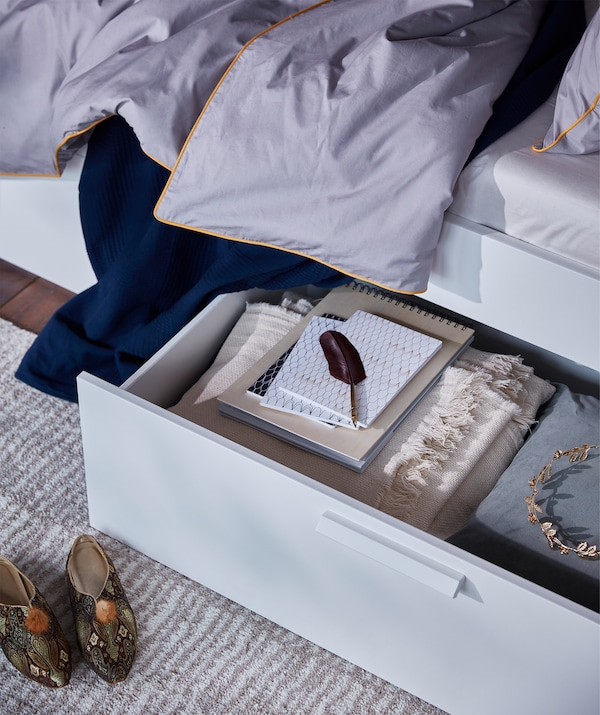 A bed storage box filled with things you might need, under the white BRIMNES bed frame with storage and headboard.