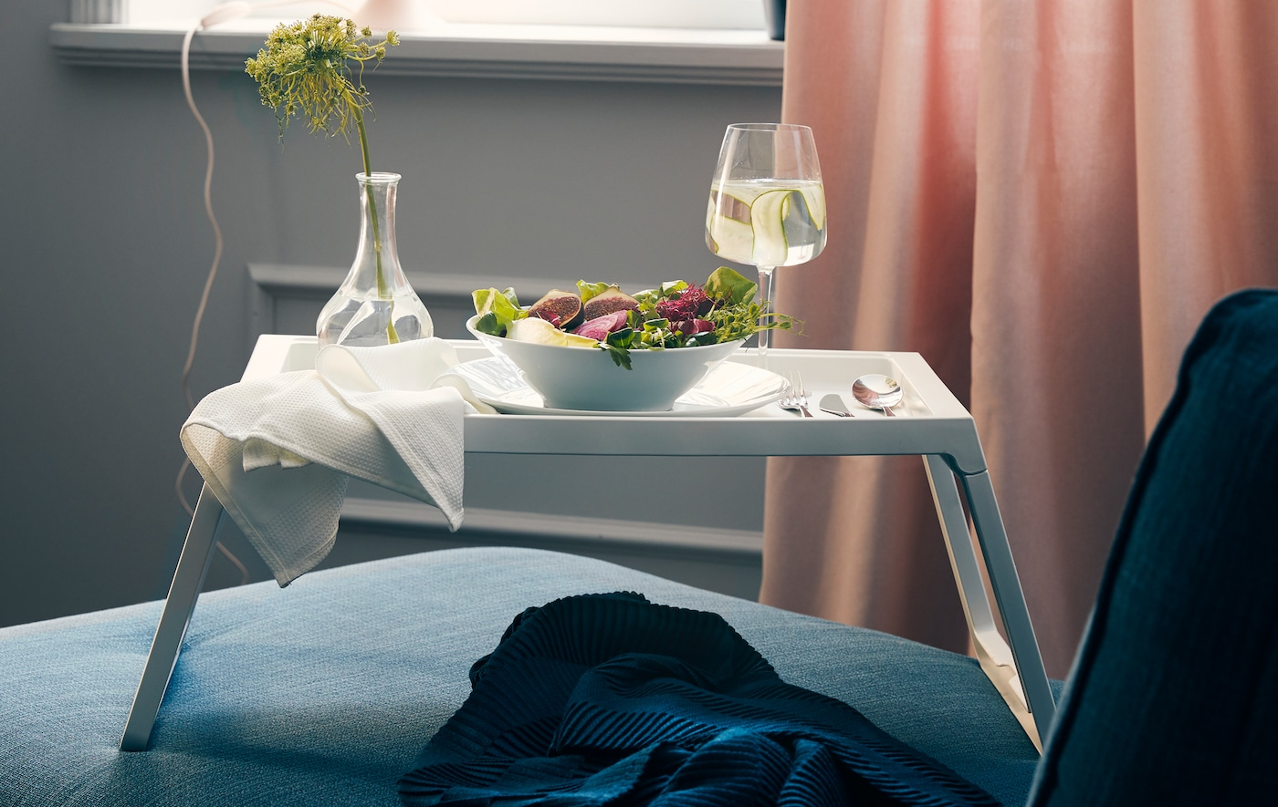 A bed tray sitting on a chaise with a salad, eating utensils, a glass of wine, and a small vase with a flower.