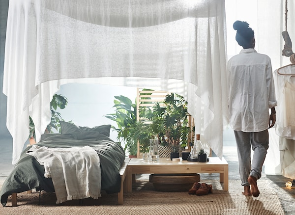 A bed under a white draped canopy with indoor plants.