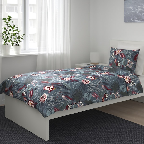 A bed with a colorful flowered pattern bed linen.