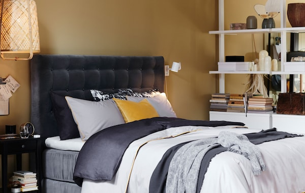 A bed with a grey velvet quilted headboard and layered bedlinen.