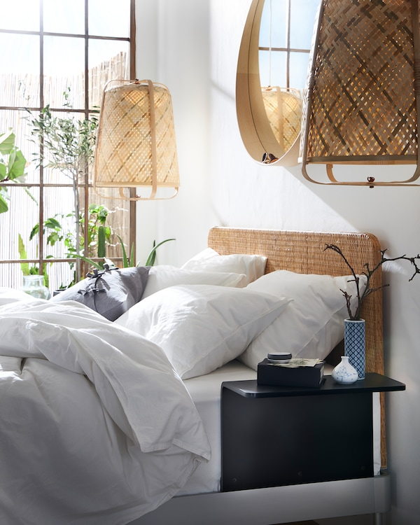 A bed with a rattan headboard and a white quilt cover and pillowcases. Pendant lamps in bamboo hang on each side of the bed.