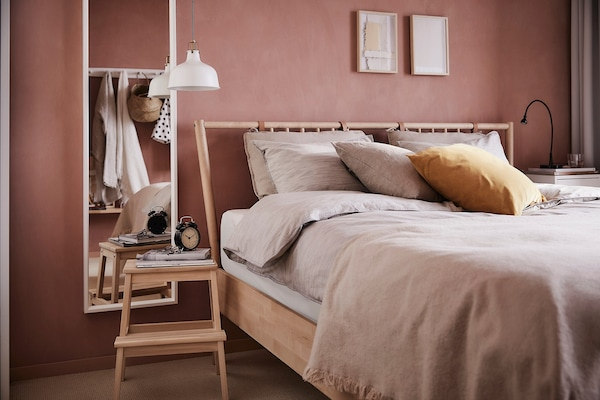 A bed with a wooden frame with footstool side table and full length mirror on a wall.