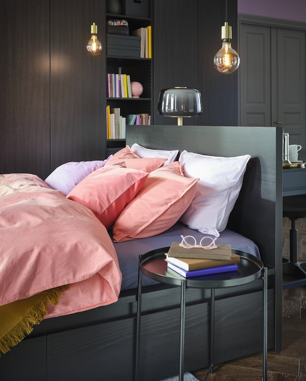 A bed with bed linen in light lilac and light brown-red. Pendant lamps hang above and a black round side table stands beside.