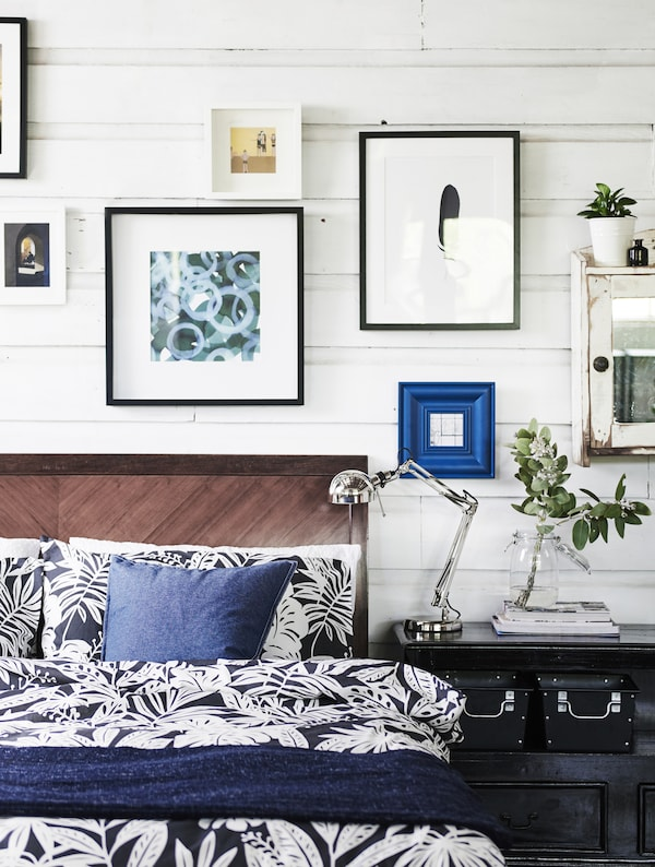 A bed with blue and white bedding and a gallery wall above.