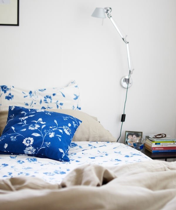 A bed with blue and white floral bedding and a silver reading lamp on the white wall above.