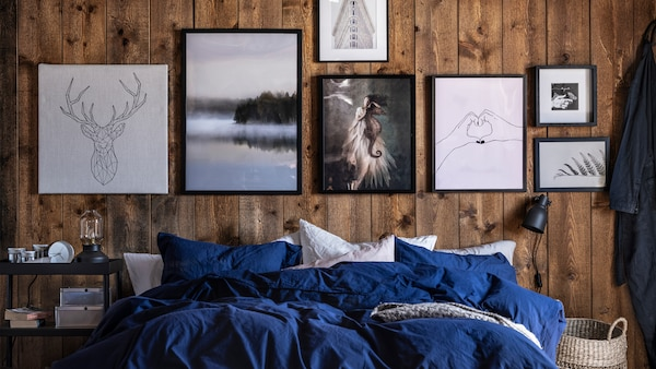 A bed with blue/white bed linen in front of wooden walls decorated with various pictures in shades of black, white and grey.