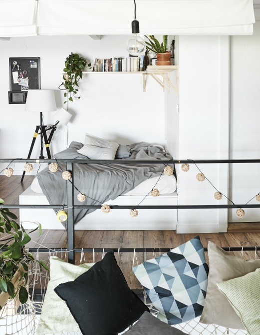 A bed with bookshelf above it and cushions on a large hammock.