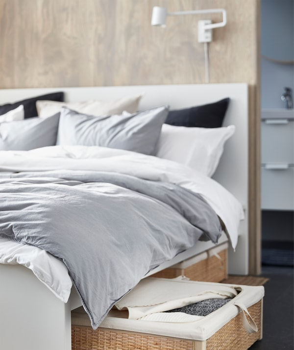 A bed with gray and white bedding and a rattan storage box underneath.
