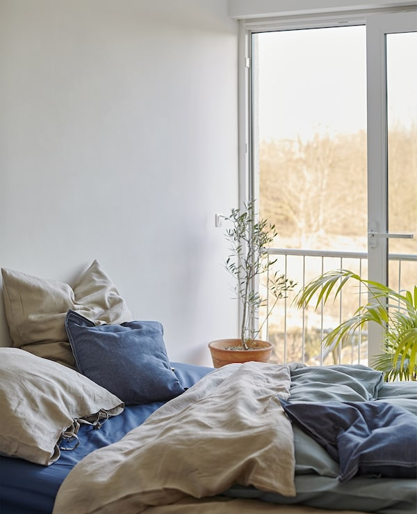 A bed with layered bedding in natural colours.