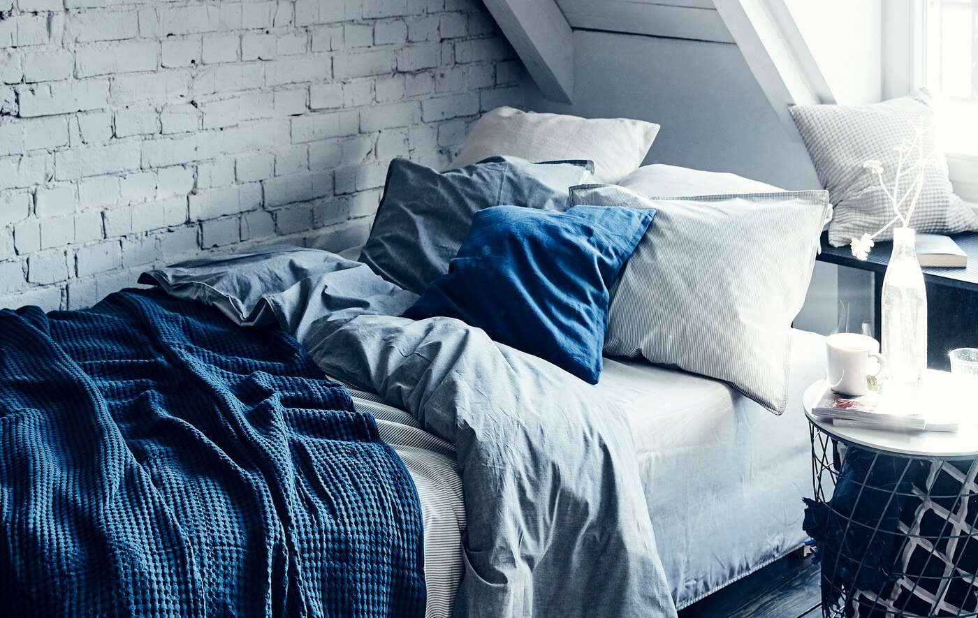 A bed with layered blue and white bedding and cushions against a white painted brick wall.