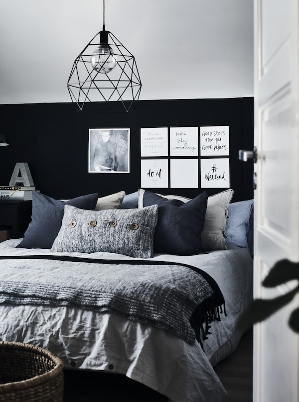 A bed with lots of cushions in different sizes, material and grey colours against a black and grey wall.