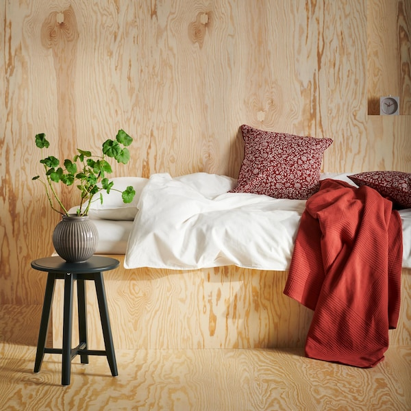A bed with red and white textiles in a pine-paneled room.