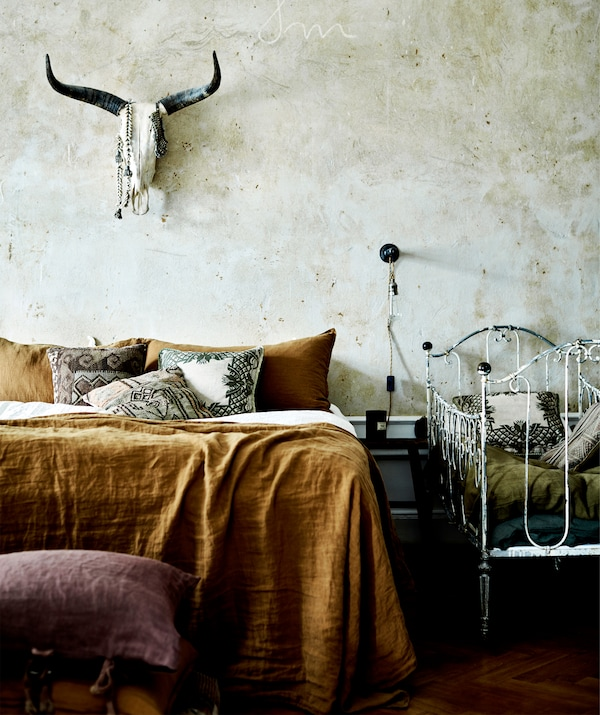 A bed with rust-coloured sheets next to a white metal crib, with an animal skull on the wall above.