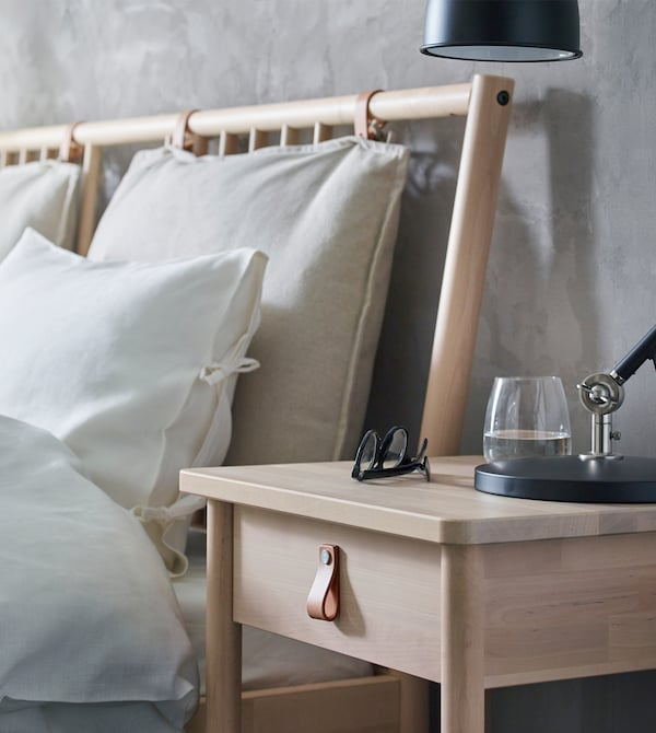 A bed with white linen and wooden bedside table with leather drawer handle.