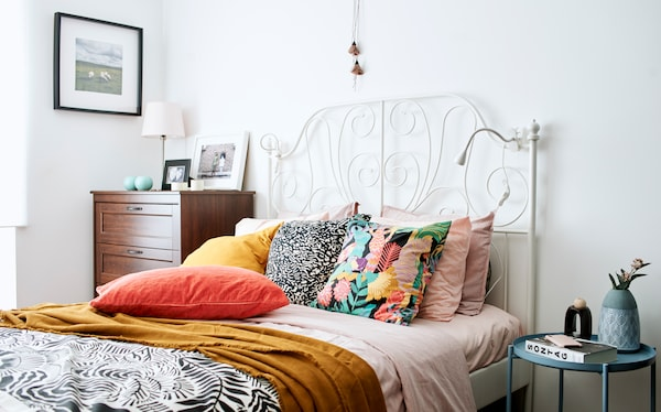 A bed with white wrought-iron bed head, a pink duvet, dark yellow throw and pillows in pink, orange, gold and monochrome.