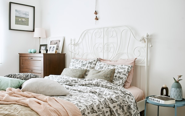 A bed with white wrought-iron bed head, dressed in a duvet with monochrome butterfly drawings, pink knit throw and cushions.