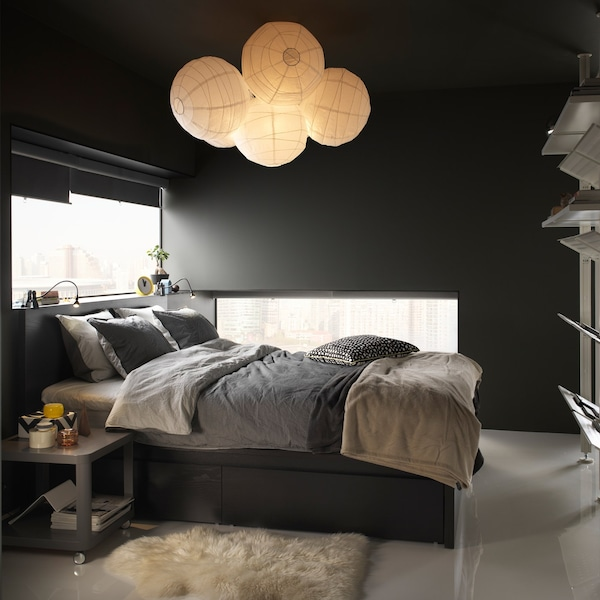 A bedroom area with an IKEA BLÅVINDA grey chambray quilt cover and pillowcases and balloon rice lamps.