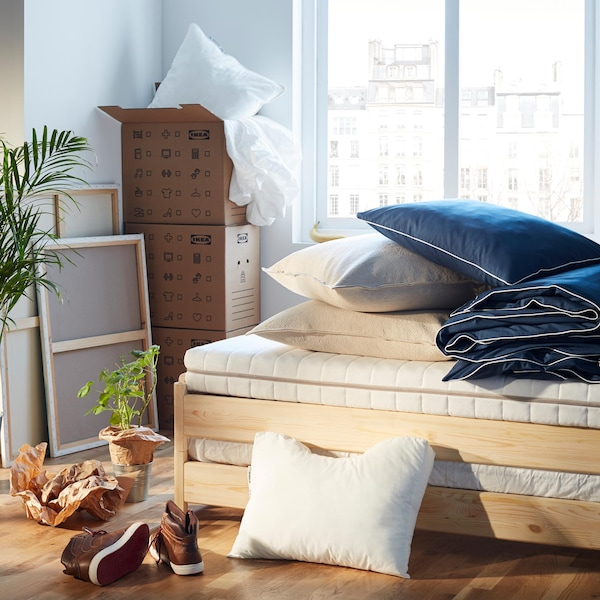 A bedroom being unpacked, with pillows, a duvet, and moving boxes.