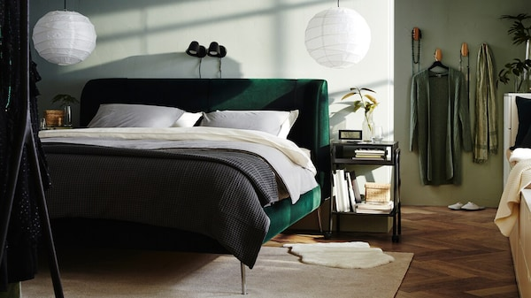 A bedroom containing a green TUFJORD bed with REGOLIT lampshades above and NORDLI drawer units with books by the windows.